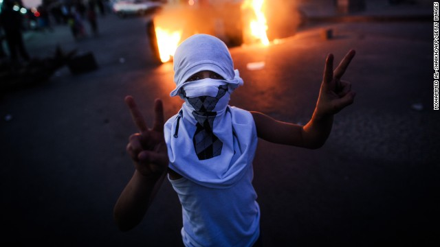 A Bahraini boy flashes the v-sign during the funeral of 10-year-old Ali Jaffer Habib, in the village of Malikiya, on August 10, 2013.