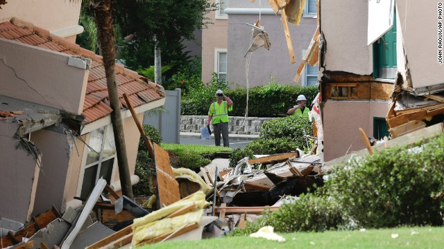 Inspectors look over damage to buildings caused by a sinkhole 40 to 50 in diameter at the Summer Bay Resort, Monday, Aug. 12, 2013, in Clermont, Fla.  Lake County Fire Rescue Battalion Chief Tony Cuellar says about 30 percent of the three-story structure at Summer Bay Resort collapsed around 3 o'clock this morning. Another section was sinking. (AP Photo/John Raoux)
