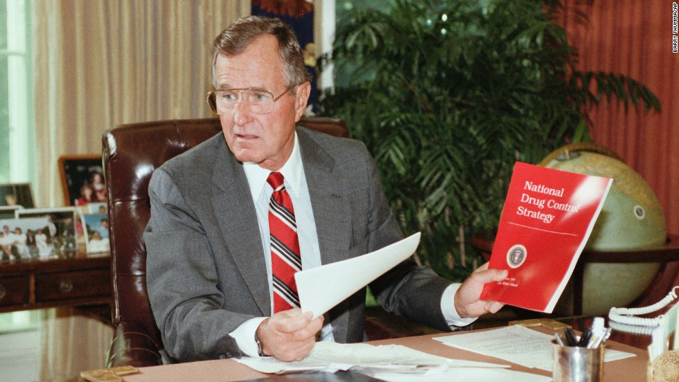President George H. Bush holds up a copy of the National Drug Control Strategy during a meeting in the Oval Office on September 5, 1989. In a televised address to the nation, Bush asked Americans to join the war on drugs.