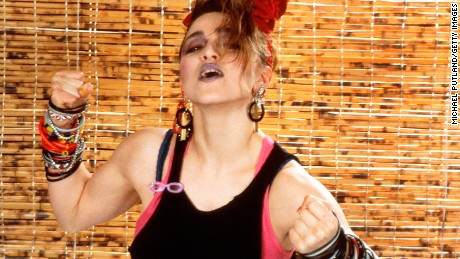 Madonna's look in 1984 - layered tops, dark makeup and bracelets, bracelets and more bracelets.