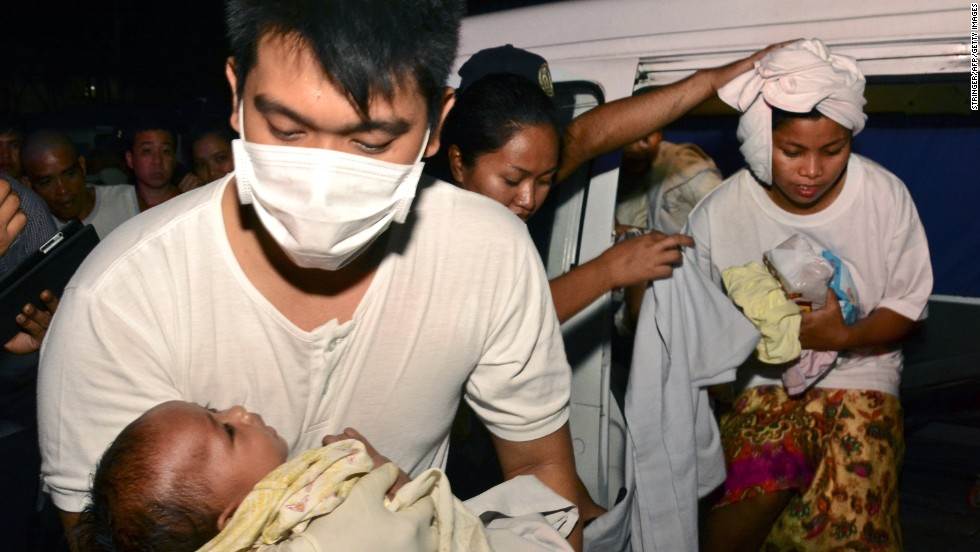 A medic carries 3-month-old Trisia Mae Kumaro as her mother steps out of an ambulance at the hospital on August 17.