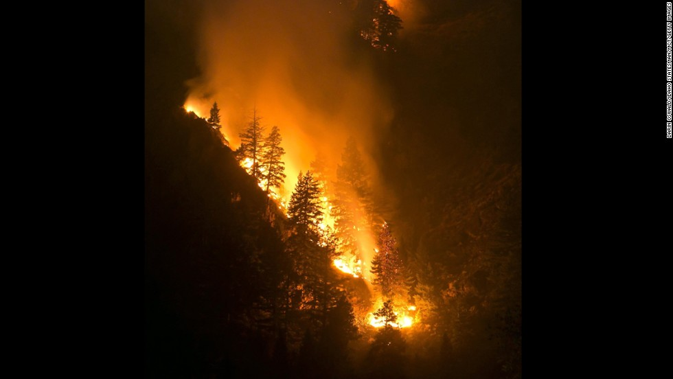 Fire creeps down the western canyon wall above the Wood River in Hailey, Idaho, on August 17.