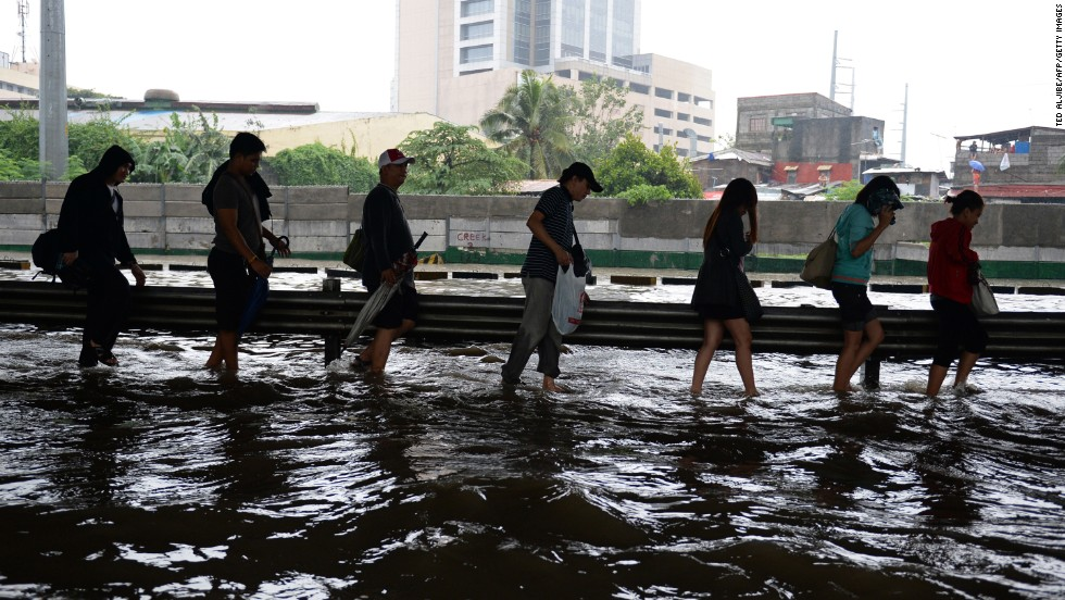 People walk along a flooded highway as heavy rains hit Manila on August 20.