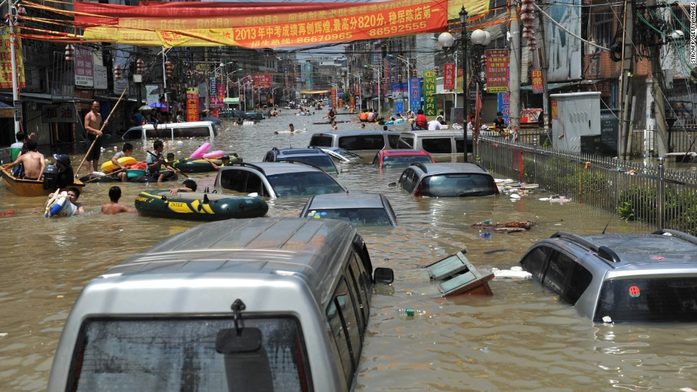 People walk through debris and vehicles submerged in floodwaters in Shantou on August 19.