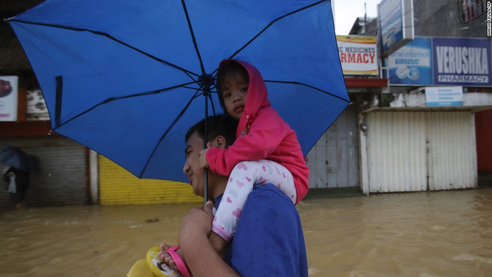 A man and a little girl evacuate to higher ground in Marikina City on August 20.