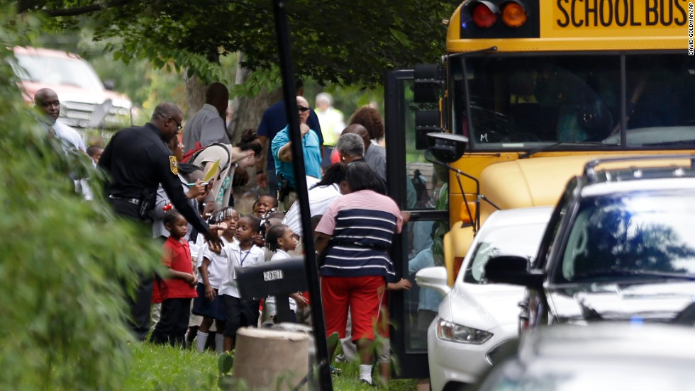 A police officer interacts with students as they board school buses to take them to reunite with their parents.