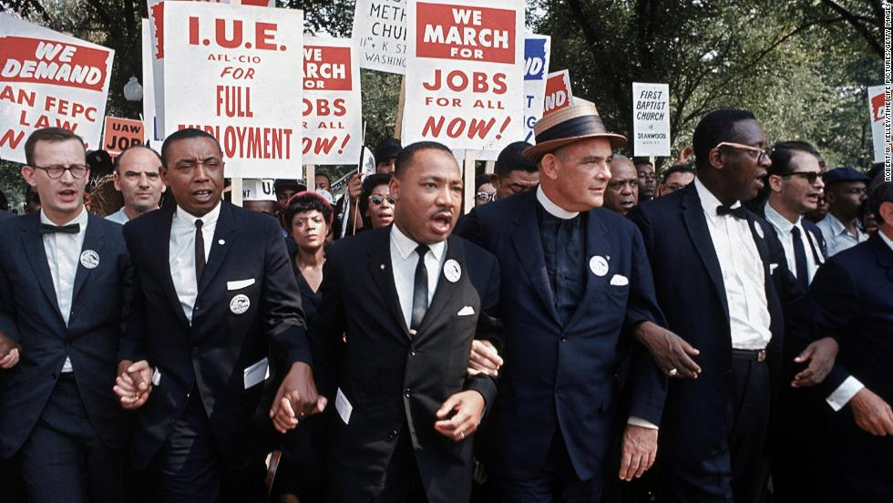 Leaders of the rally, including King in the center, interlock hands and arms as they march. The march was organized jointly by James Farmer, of the Congress of Racial Equality; Dr. King, of the Southern Christian Leadership Conference; John Lewis, of the Student Nonviolent Coordinating Committee; A. Philip Randolph, of the Brotherhood of Sleeping Car Porters; Roy Wilkins, of the National Association for the Advancement of Colored People; and Whitney Young, Jr., of the National Urban League.