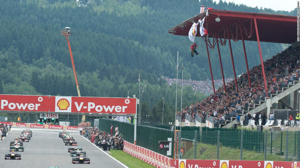 "Drivers perform a warm-up lap at the Spa-Francorchamps circuit as Greenpeace militants deploy a banner reading ""ARCTIC OIL? SHELL NO!"""