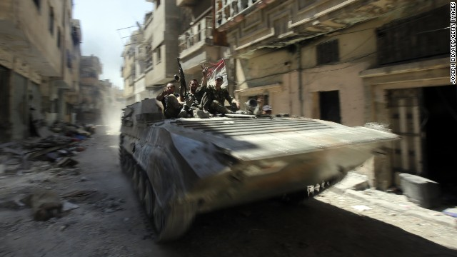 Soldiers of the Syrian government forces patrol on a tank in a devastated street on July 31, 2013 in the district of al-Khalidiyah in the central Syrian city of Homs. The Syrian government announced the capture of Khalidiyah, a key rebel district in