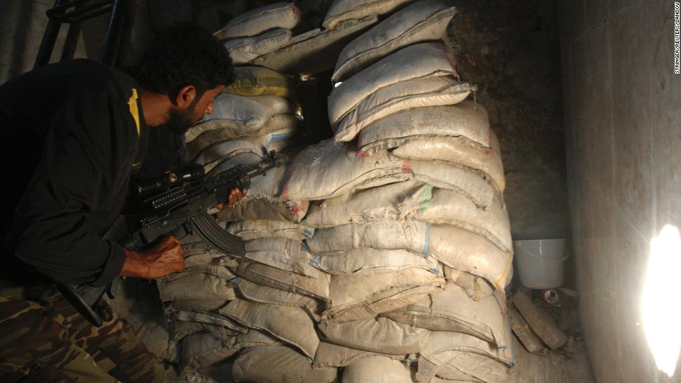 A Free Syrian Army fighter takes position behind sandbags in the old city of Aleppo, Syria, on Tuesday, August 27.