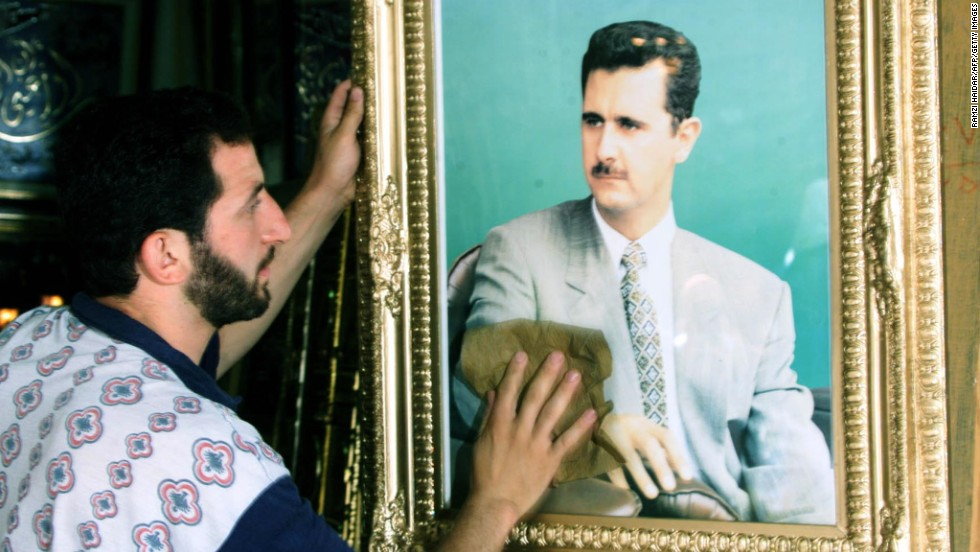 A shopkeeper cleans a portrait of al-Assad in Damascus on June 20, 2000, as the ruling Baath Party prepared to wind up its historic congress by consecrating al-Assad as its secretary-general and choosing a new leadership body.