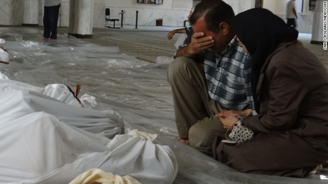 A Syrian man mourns over the bodies of those killed in an alleged chemical weapons attack in Damascus, Syria, in 2013.