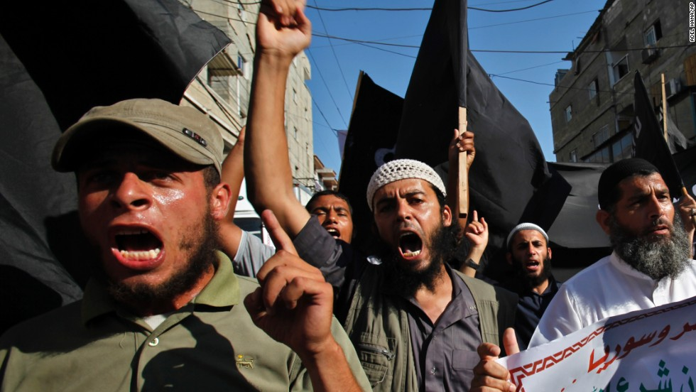 A group of young Salafists chants and waves black flags during a protest against the Egyptian and Syria regimes in the southern Gaza Strip on August 22.