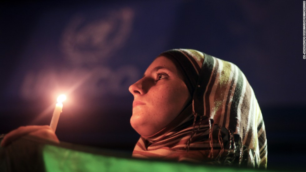 "A young woman holds a Syrian revolution flag and a candle during a protest of President Bashar al-Assad in front of the U.N. headquarters in Gaza City on Friday, August 23. U.N. Secretary-General Ban Ki-moon intends to conduct a ""thorough, impartial and prompt investigation"" into the alleged chemical weapons attack in Syria."