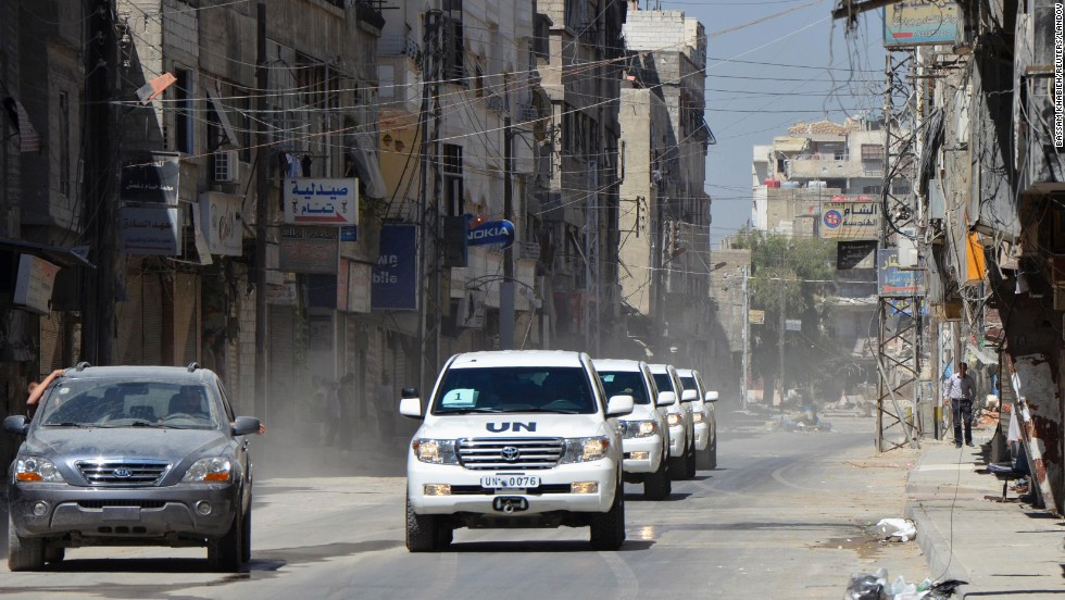 Free Syrian Army fighters escort U.N. vehicles with chemical weapons experts on August 28 through a site of a suspected chemical weapons attack outside Damascus.