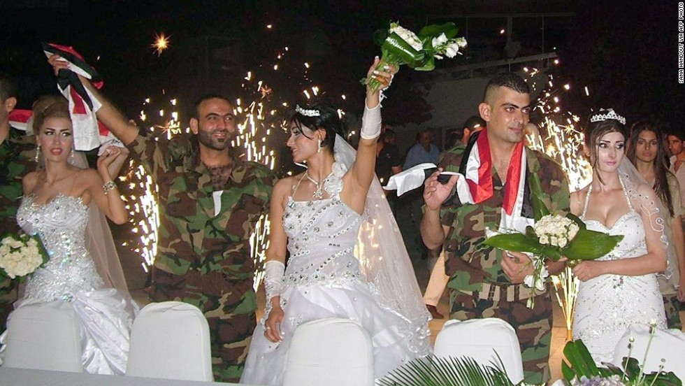 Syrian soldiers celebrate with their their brides during a group wedding in Latakia province.