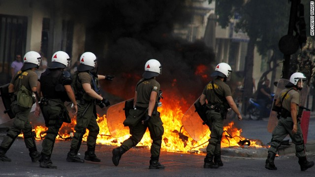 Riot police walk past blazing flames in Athens on August 16, 2013, as they clash with protesters during a demonstration.