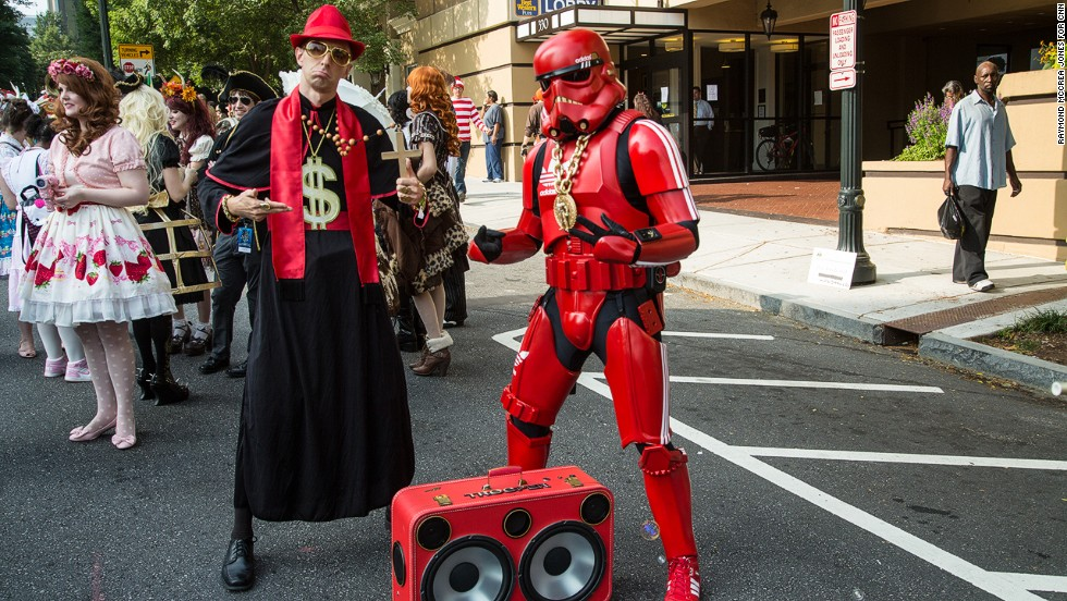 People dressed as the Pimp Priest and the Hip-Hop Stormtrooper attend the parade.