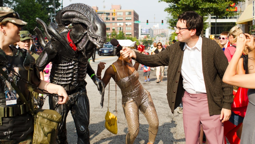 "A person in character as the creature from the ""Alien"" films is interviewed during the parade."