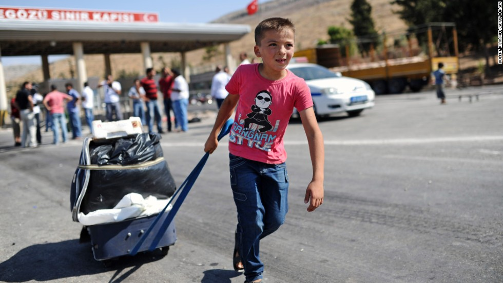 A child pulls a suitcase as Syrian refugees arrive at the Cilvegozu crossing gate in Turkey in August 2013.
