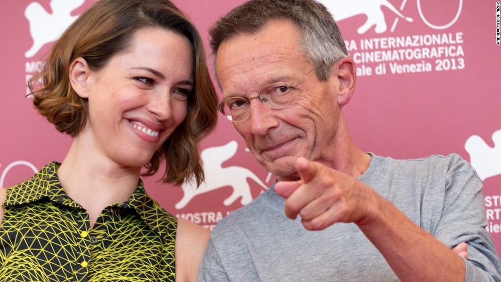 "Director Patrice Leconte, right, points at photographers while posing with actress Rebecca Hall during the photo call for the film ""A Promise"" on September 4."