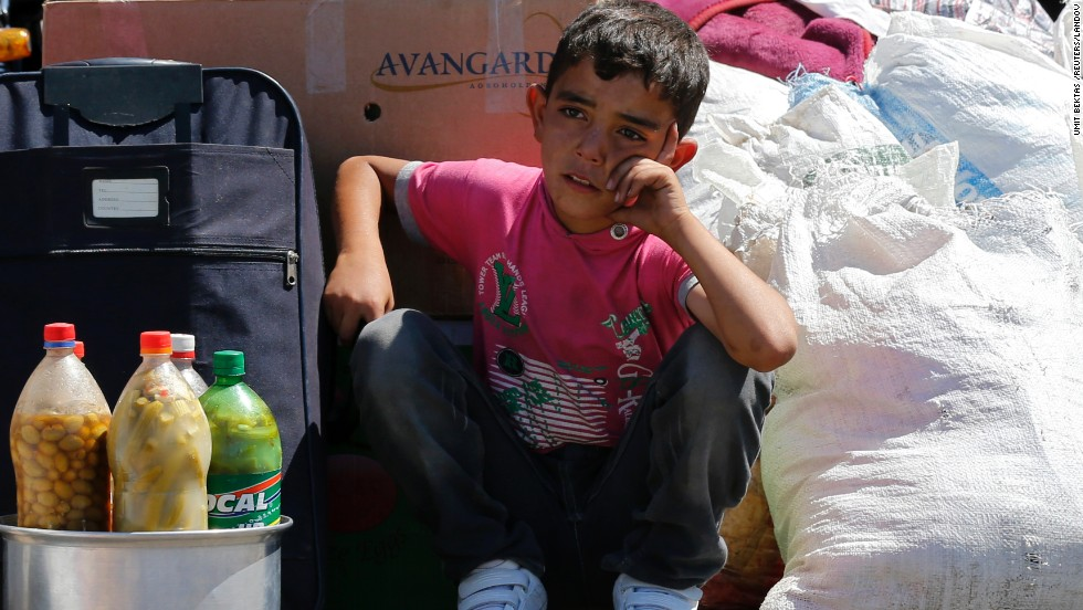 A Syrian boy sits beside his family's belongings in September 2013 as they wait for a vehicle to pick them up after entering Turkey.