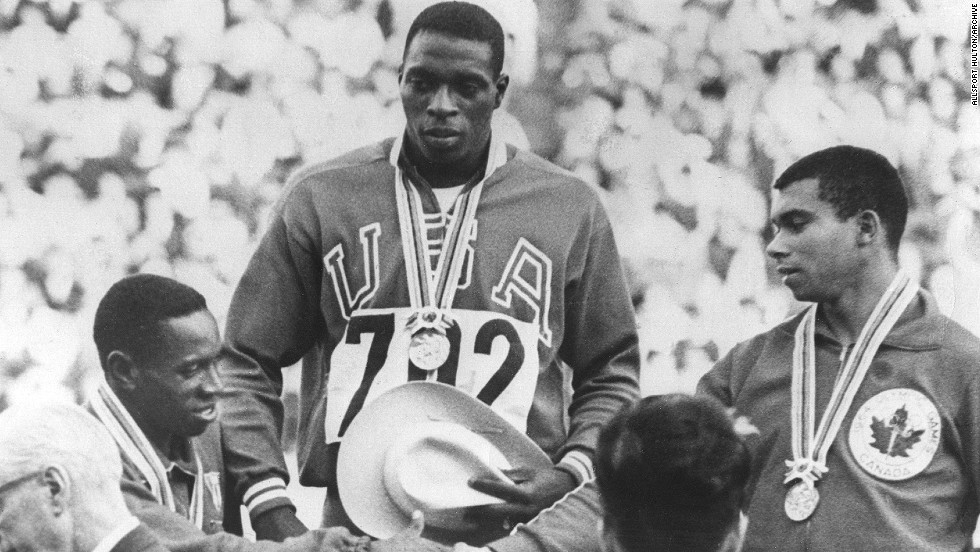 October 15, 1964: Robert Hayes of the U.S. (center) stands on the podium after receiving his gold medal for winning the men's 100 meter final. Silver medal winner Enrique Figuerola of Cuba (left) congratulates Harry Jerome of Canada, who came third. Hayes' time of 10.0 seconds was a new Olympic record.