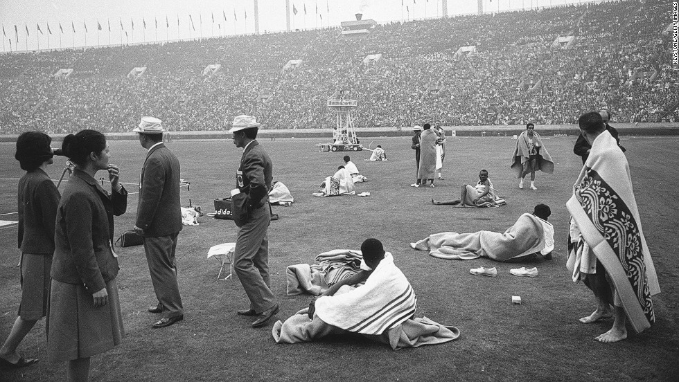 October 21, 1964: Marathon runners keep warm in patterned blankets after the race.