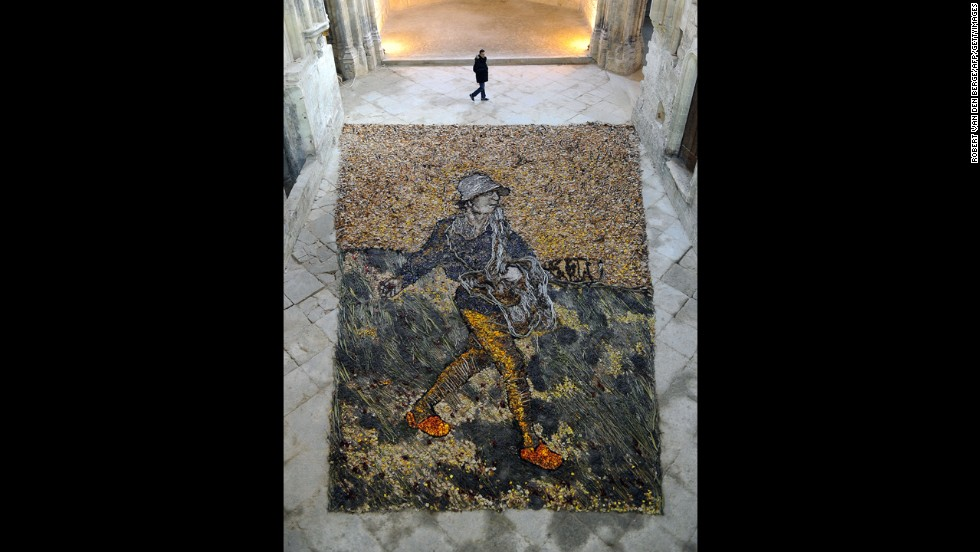 "A man walks past a recreation of van Gogh's ""The Sower"" made by Brazilian artist Vik Muniz with branches, leaves and dried flowers."