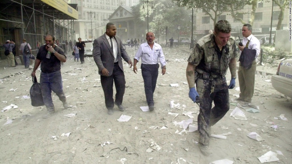 People walk in the debris-covered streets near the World Trade Center towers on September 11, 2001.