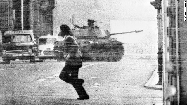 SANTIAGO, CHILE: Chilean crossing a street in Santiago, behind a military tank which is on his way to the Presidential Palace, Santiago, 30 June 1973. The revolt against President Salvador Allende crushed, but in September 1973, a career army officer, Augusto Pinochet, led a military coup which overthrow the Allende government. Allende died in his palace, 11 september 1973 and Pinochet established himself as the head of the ensuing military regime.