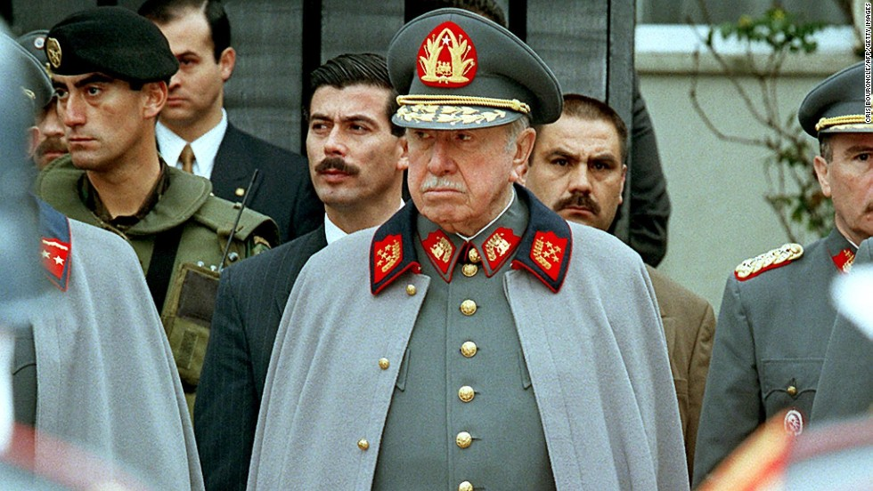 Pinochet listens to a military band playing before his residence in Santiago on September 11, 1997 to commemorate the 24th anniversary of the coup.