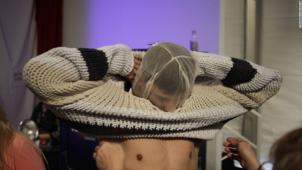 A model puts on a face net to protect his makeup during an outfit change at the Nautica show.