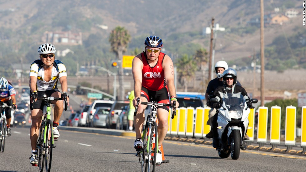 "Mogle stays strong during the cycling leg of the race. He was the first of the Fit Nation team to cross the finish line, but says simply finishing is <a href=""http://www.cnn.com/2013/07/19/health/fit-nation-mogle-finishing/index.html"">no longer his goal.</a>"