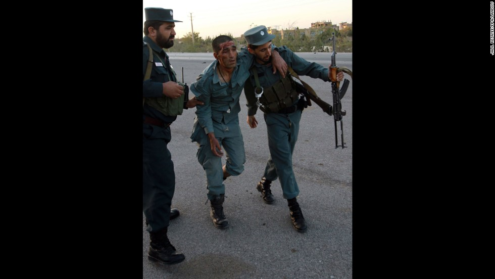 Afghan security officials help an injured colleague  on September 13.