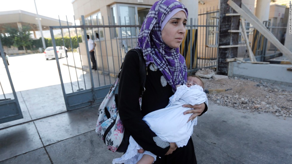 A Syrian woman carries her baby across the border into Turkey at the Cilvegozu border gate in September 2013.