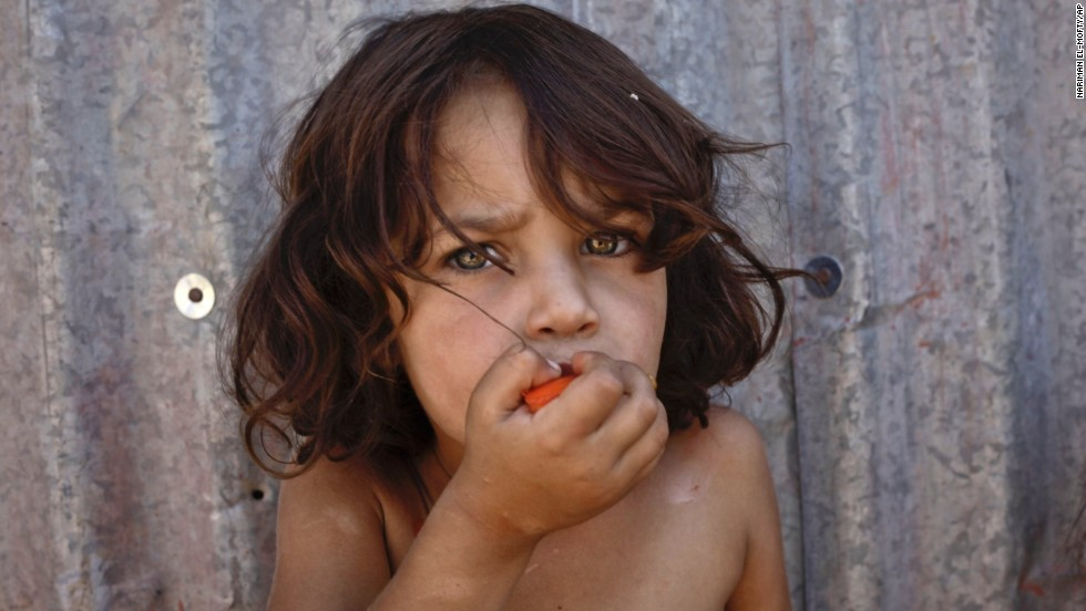 A Syrian girl eats a tomato at a temporary refugee camp in the eastern Lebanese town of al-Faour in September 2013.