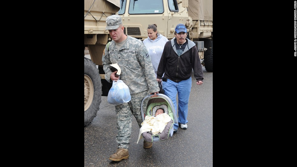 Colorado Army National Guard Sgt. David Wilson carries Ezra Villa while escorting Thomas Walter and Melinda Villa to the flood evacuation area in Lyons on September 13.