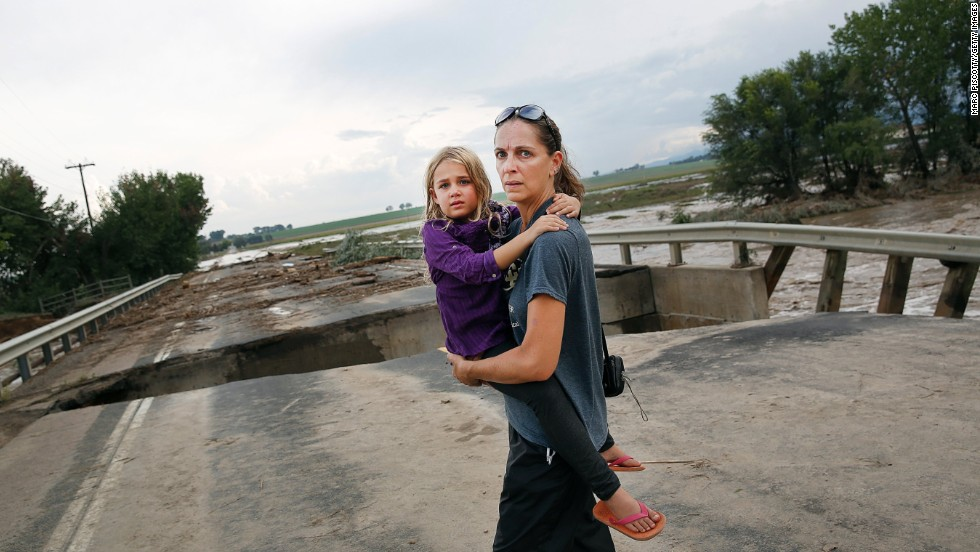 Samantha Kinzig of Longmont, Colorado, and her 5-year-old daughter, Isabel, take a closer look at the damaged bridge on Weld County Road 1 on September 13.