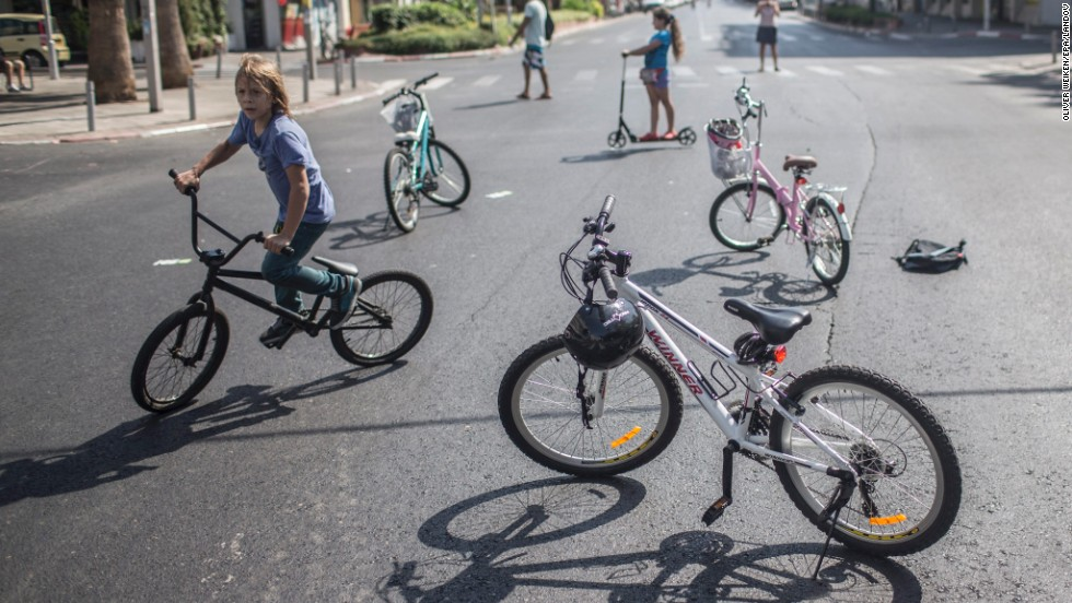 Israeli children ride their bikes on an empty street during Yom Kippur in Tel Aviv.