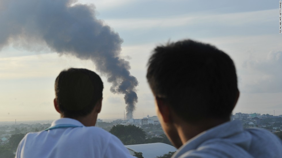 Two men watch as smoke billows from burning houses as firefight between government troops and Muslim rebels rages in Zamboanga City, on September 16. Sporadic clashes continued as soldiers moved to clear Moro National Liberation Front (MNLF) gunmen from coastal neighbourhoods after a ceasefire plan collapsed.
