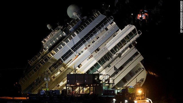 The Costa Concordia ship lies on its side on the Tuscan Island of Giglio, Italy, Monday, Sept. 16, 2013. Using a vast system of steel cables and pulleys, maritime engineers on Monday gingerly winched the massive hull of the Costa Concordia off the reef where the cruise ship capsized near an Italian island in January 2012. But progress in pulling the heavily listing luxury liner to an upright position was going much slower than expected. Delays meant the delicate operation — originally scheduled from dawn to dusk Monday — was not expected to be completed before Tuesday morning. (AP Photo/Andrew Medichini)
