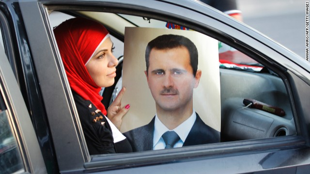 A Syrian woman holds a portrait of Syria's President Bashar al-Assad as pro-regime supporters parade their cars in Damascus to celebrate Assad's 48th birthday on September 11, 2013.