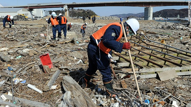 Police officers search for tsunami victims two years after the disaster in Ishinomaki, Miyagi prefecture on March 11, 2013.
