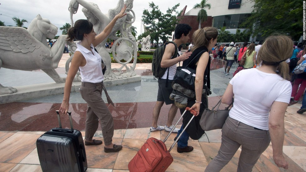 Tourists wait in line at an improvised check-in counter at an airport in Acapulco on September 17.