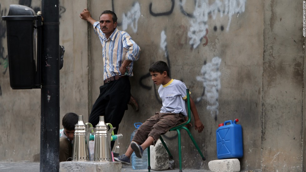 Young Syrian refugees sit with their father as he prepares coffee to sell on a street in Beirut in September 2013.