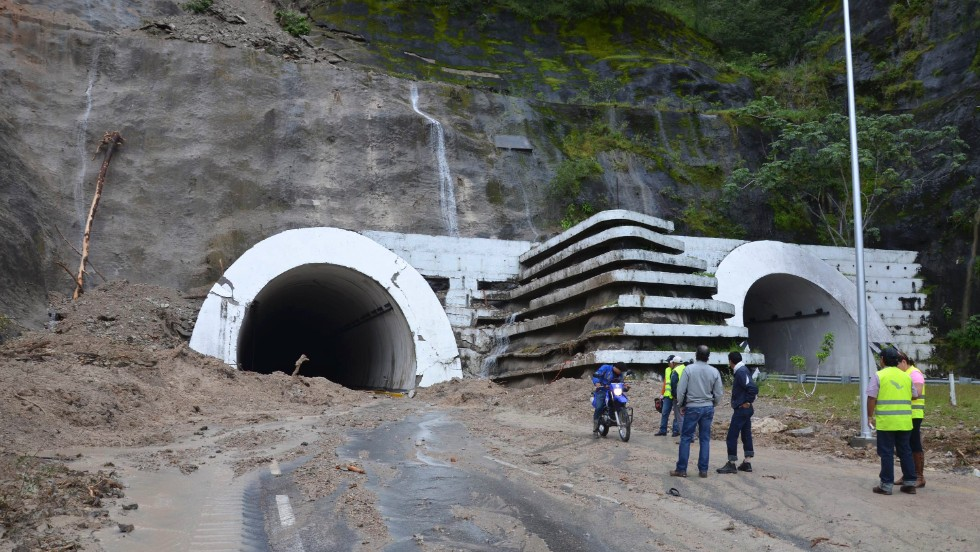 People stand at the entrance of the Agua de Obispo tunnel that connects Acapulco with Chilpancingo, Mexico. The tunnel was badly damaged by the flooding.