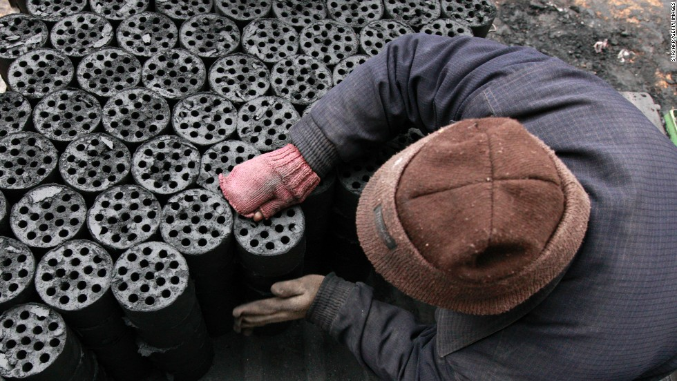 A worker moves coal briquettes onto a pedicab at a coal distribution business in central China's Anhui province in January 2013. Environmental concerns -- particularly over the use of coal -- have been pushed to the top of the national agenda after record air pollution in the past year.