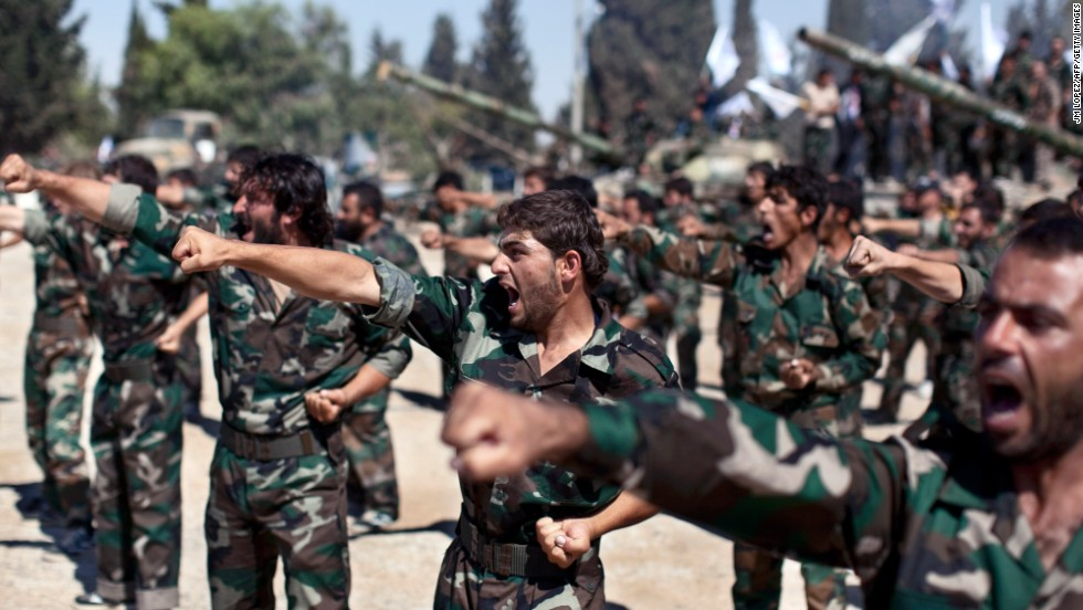 Rebels parade at a former military academy north of Aleppo during a September 13 ceremony to mark an agreement to unite two rebel brigade forces.