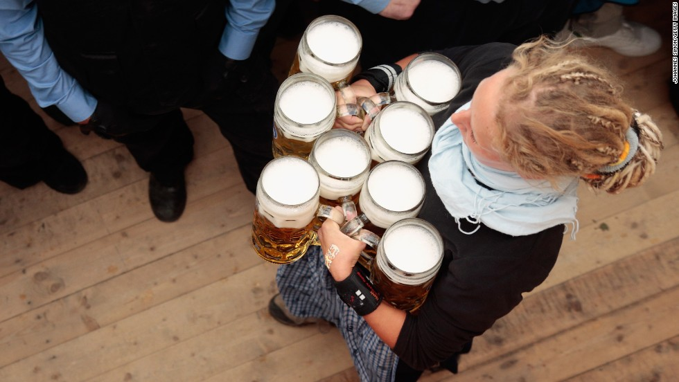 A waitress delivers mugs of beer after tapping the first barrel.
